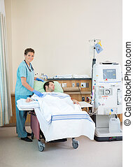 Portrait of female nurse standing by patient receiving dialysis in hospital room