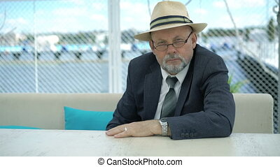 Portrait of old businessman sitting at table outdoor and looking on camera. 4K