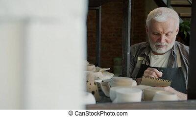 Portrait of old craftsman counting ceramics in workshop ...