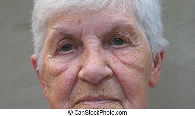 Portrait of old grandmother with a sad sight. Wrinkled face...