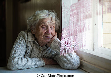 Portrait of old lady sitting at the table. Pensioner.