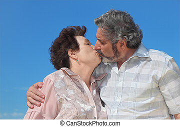 portrait of old man and woman kissing lips, blue sky