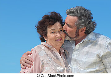 portrait of old man embracing woman and kissing her cheek, blue sky
