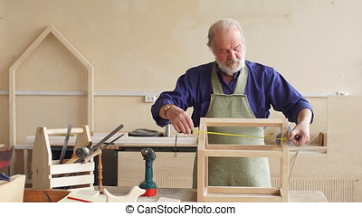 Portrait of old repairman working with wooden board.