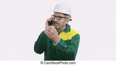 Portrait of old senior business man in suit and helmet Isolated over white background talking on the phone.