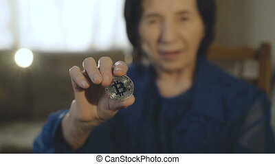 Portrait of old smiling woman holds a silver bitcoin in hand at camera