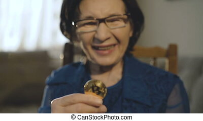 Portrait of old woman holds a golden bitcoin in hand at camera