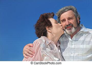 portrait of old woman kissing man cheek, blue sky