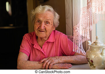 Portrait of old woman sitting at the table.