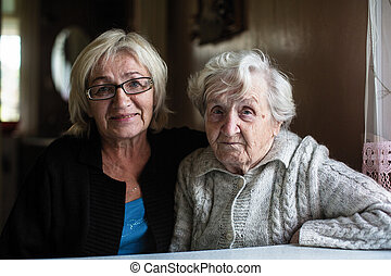Portrait of old woman with her adult daughter.