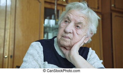 Portrait of old wrinkled tired alone grandmother looking at camera.