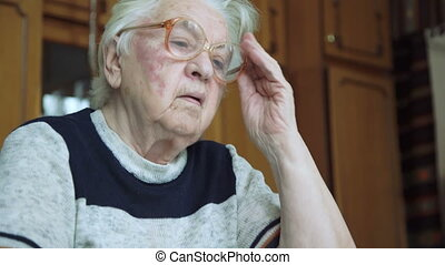 Portrait of old wrinkled tired alone grandmother looking at...