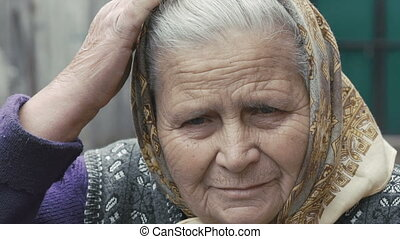 Portrait of old wrinkled tired grandmother smiling and looking at camera