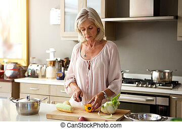 older woman in kitchen preparing healthy meal