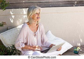 older woman sitting outside working on laptop