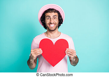 Portrait of optimistic cool guy showing paper heart wear pink cap t-shirt spectacles isolated on teal color background