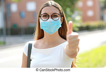 Portrait of optimistic girl wearing protective mask showing thumb up in city street