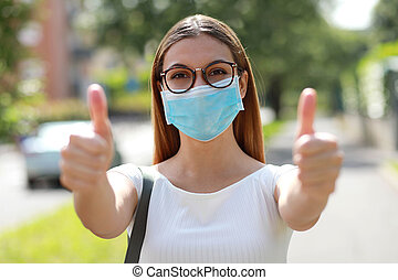 Portrait of optimistic girl wearing protective mask showing thumbs up in city street