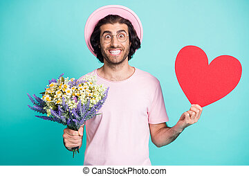 Portrait of optimistic handsome guy hold flowers paper heart wear pink cap t-shirt spectacles isolated on teal color background