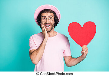 Portrait of optimistic hipster guy hand on cheek hold paper heart wear pink cap t-shirt spectacles isolated on teal color background