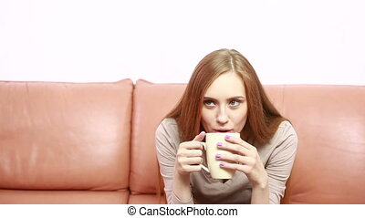 Portrait of oung beautiful woman with a cup on sofa
