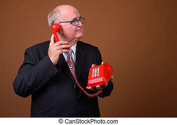 Portrait of overweight senior businessman talking on phone