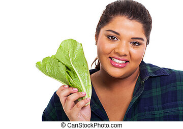 portrait of overweight teenage girl holding lettuce