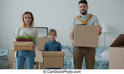 Portrait of parents and cute child holding boxes looking at camera with happy faces during relocation to new house. Family life and apartment concept.