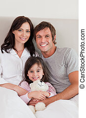 Portrait of parents posing with their daughter