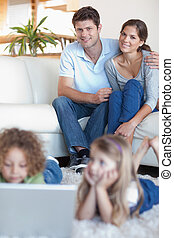 Portrait of parents watching their children using a laptop