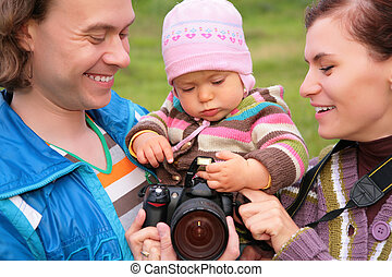Portrait of parents with baby in nature with photocamera