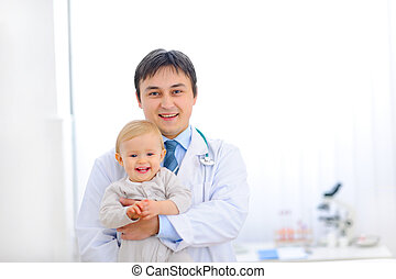 Portrait of pediatric doctor holding smiling lovely baby