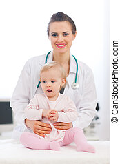 Portrait of pediatric doctor with baby looking on side