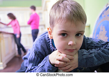 portrait of pensive boy on kitchen against background of...