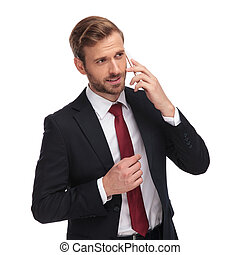 pensive businessman talking on the phone and looking to side