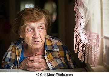 Portrait of pensive elderly woman looking out the window.