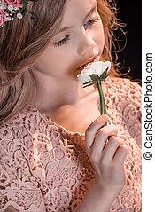 portrait of pensive girl holding flower in hand on black