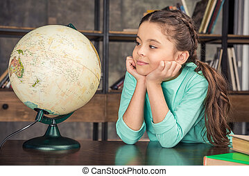 portrait of pensive girl looking at globe in library