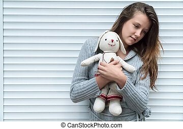 Portrait of pensive girl with a toy