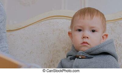 Portrait of pensive little boy at home.