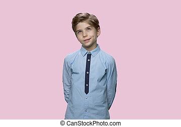 Portrait of pensive little boy on color background.
