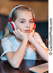 portrait of pensive little girl listening music in headphones