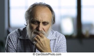 Portrait of pensive old man pondering over life