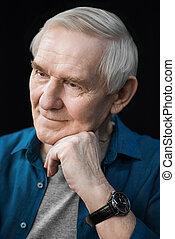 portrait of pensive smiling senior man on black