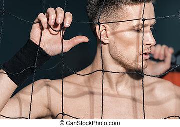 pensive sporty man standing near net