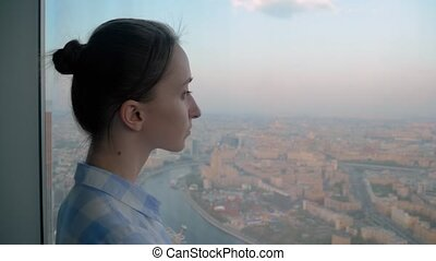 Portrait of pensive woman looking at cityscape through window of skyscraper