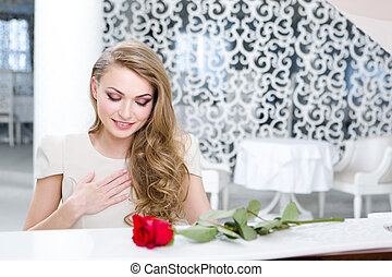 Portrait of pianist with red rose playing piano