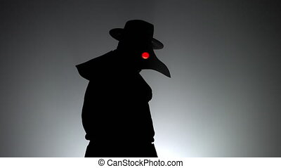 Portrait of plague doctor with crow-like mask and red eyes isolated on black smoke background. Creepy mask, halloween, historical terrible costume concept. Epidemic. High quality 4k footage