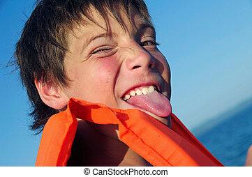Portrait of   playful cute  boy showing tongue
