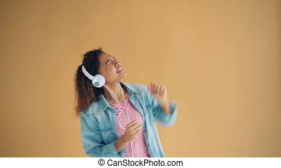 Portrait of playful girl in headphones listening to music dancing and singing